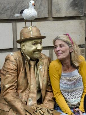 Woman sitting beside a street performer
