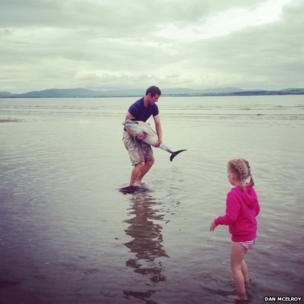 Man carrying dolphin watched by little girl. Photo: Dan McElroy