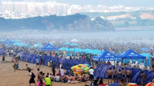 People cool off on a beach in Qingdao, in eastern China's Shandong province (11 Aug 2013)