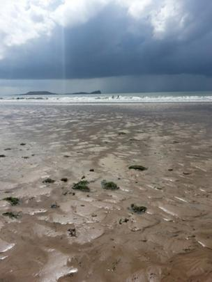 A view across Rhossili beach on Gower, Swansea, to Worm's Head