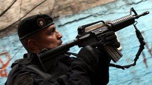 A member of Special Police Operations Battalion raids a slum