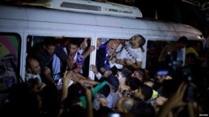 People greet Palestinian prisoners inside a bus in northern Gaza, near the Erez crossing (13 August 2013)