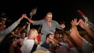 A freed Palestinian prisoner is greeted by a crowd in Ramallah (13 August 2013)