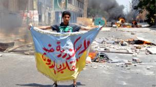 "A supporter of the Muslim Brotherhood and Egypt's ousted president Mohammed Morsi holds a banner reading in Arabic ""Alexandria is against the coup"" as protestors set fire to a council building in Egypt's northern coastal city of Alexandria on 14 August 2013"