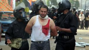 Egyptian riot police arrest a wounded demonstrator during clashes as security forces disperse protest camps on 14 August, 2012 that were set up in Cairo by supporters of Egypt's ousted President Mohamed Morsi