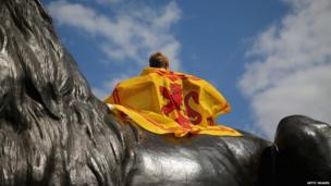 A Scotland fan sits on a statue in Trafalgar Square