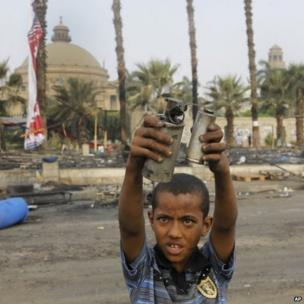 An Egyptian child displays empty tear gas canisters among the debris of the protest camp in Nahda Square near Cairo University, 15 August.