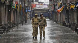 Indian policemen patrol a deserted street in Srinagar city in Indian-administered Kashmir during a strike called by separatists to mark India's Independence Day on 15 August