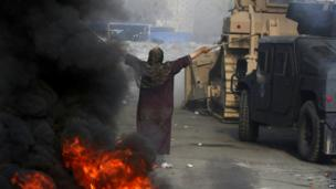 An Egyptian woman tries to stop a military bulldozer on Wednesday 14 August 2013 as security forces cleared camps occupied by supporters of deposed president Mohamed Morsi. Hundreds of people were killed in the bloodiest day in Egypt since the pro-democracy uprising two years ago.