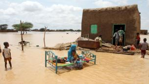 A Sudanese woman sits next to a house in a flooded street on the outskirts of the capital Khartoum, Sudan - Saturday 10 August 2013