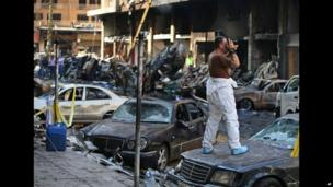 An army photographer in Beirut, Lebanon, amidst the wreckage of cars - Friday 16 August 2013