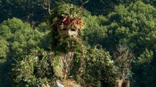 A towering Green Man watches over festival goers in Powys