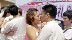 Newly-wed couples kiss during the traditional Qixi Festival, China's version of Valentine's Day that is a popular day for marriages on 13 August, 2013.