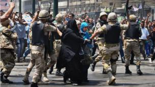 Egyptian security forces escort supporters of the Muslim Brotherhood, centre, out of the al-Fath mosque and through angry crowds (17 August 2013)