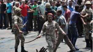 Egyptian security forces try to keep angry crowds away from the al-Fath mosque in Cairo (17 August 2013)