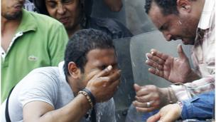 Police and pro-Egyptian government supporters fight the effect of tear gas outside al-Fath mosque in Cairo (17 August 2013)