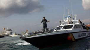 A member of the Spanish Civil Guard tries to calm down a Spanish fisherman (not pictured) in his fishing boat taking part in a protest