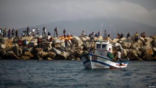 Men wave Spanish national flags during a protest by Spanish fishermen at the site where an artificial reef was built by Gibraltar with concrete blocks