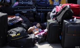 A Palestinian boy sleeps amidst suitcases at the Rafah crossing between Egypt and the southern Gaza Strip