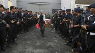 Armed Indonesian police officers watch an inmate carrying his belongings as he leaves to be transferred to another prison