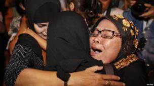 A Thai citizen (C) who was evacuated from Egypt embraces her family as she arrives at Don Muang International Airport airport in Bangkok