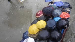 Residents use umbrellas aboard a truck after they are evacuated from their houses, swamped with floodwaters caused by monsoon rains in Sucat, Paranaque, in Manila on 19 August 2013