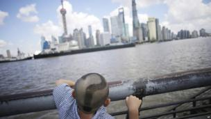 A boy with his head shaved looks at the skylines in Pudong, China's financial and commercial hub, in Shanghai, China, on 20 August 2013