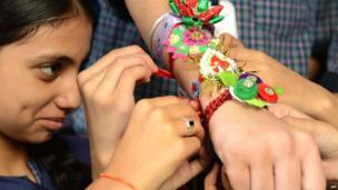 "An Indian schoolgirl ties a ""rakhi"" - sacred thread - onto the wrist of a schoolboy on the eve of the Hindu festival Raksha Bandhan at a school in Amritsar on 20 August 2013."