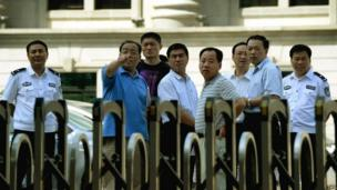 Security officials gesture as they make preparations at the Intermediate People's Court where disgraced politician Bo Xilai will soon go on trial in Jinan, Shandong Province on 20 August 2013