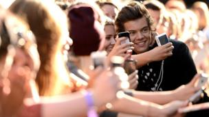 Harry Styles taking pictures with fans