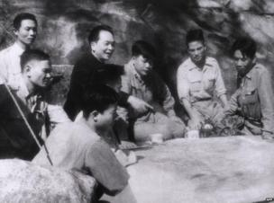 This picture taken in March 1954 shows General Vo Nguyen Giap (4th R-black top) explaining operation plans to his aids next to a military map at his PC in Dien Bien Phu.