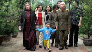 Vietnamese General Vo Nguyen Giap walks with his family in his garden in Hanoi, March 30, 2004.