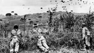 The first landed paratroopers of the French-Indochinese Union army have a watchful eye on the descent of their comrades, as Operation Castor gets under way, on November 20, 1953, in the hill tops district northwest of Hanoi .
