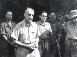 French Chief Commander of Dien Bien Phu garrison Colonel Christian de la Croix de Castries (2nd L) and his unidentified aids surrender to Vietnamese troops after the French defeat at Dien Bien Phu, 7 May 1954
