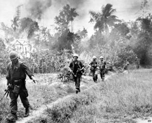 U.S. Marines leave the flaming village of Cam Ne after setting fire to about 100 homes during the Vietnam War in 1965.