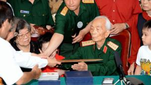 Vo Nguyen Giap (2nd R) eceives a bronze commander sword offered by Vietnamese historians during a private meeting held to mark the 60th anniversary of his nomination as Vietnam's communist army's first general