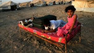 Syrian children sit on a bed at a refugee camp in northern Iraq.