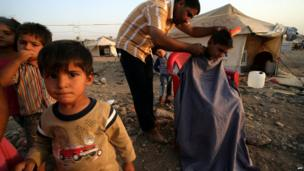 A Syrian-Kurdish man cutting the hair of a boy at the Quru Gusik refugee camp, 20 kilometres east of Irbil, the capital of the autonomous Kurdish region of northern Iraq, on 22 August, 2013.