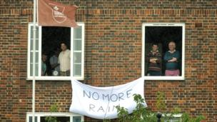 "Residents overlooking the Oval hang a ""no more rain banner"" from their windows"