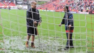 Groundsmen work on the pitch at The Valley
