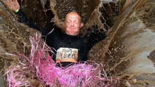 A Tough Mudder competitor splashes into a muddy pool at the Edinburgh event