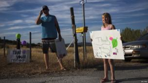 "A little girl holds a sign saying ""Thank you"" after evacuating her home in Groveland, California on 24 August 2013"
