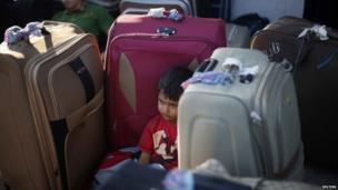 A Palestinian boy rests among suitcases as he waits to cross into Egypt at the Rafah crossing between Egypt and southern Gaza