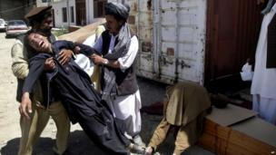 Afghans help a man mourning over his brother's death south of Kabul