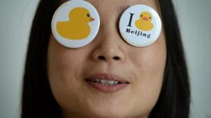 "A Chinese girl poses with ""Rubber Duck"" badges after a press conference on August 28, 2013 to announce its imminent arrival in Beijing"