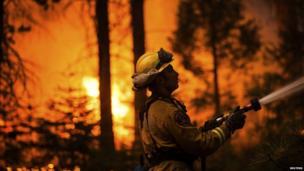 A fireman fights a raging wildfire near Camp Mather, California