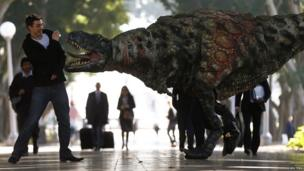 A man reacts as a performer dressed in a Tyrannosaurus rex dinosaur costume walks next to him during a publicity event in central Sydney, Australia.