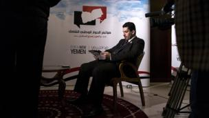 NDC Secretary General Ahmed Awad bin Mubarak reads a newspaper before a television interview