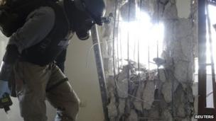 """A U.N. chemical weapons expert, wearing a gas mask, inspects one of the sites of an alleged chemical weapons attack in the Damascus"""" suburb of Zamalka August 29, 2013."""