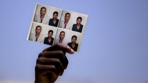 An Ethiopian Israeli holds up photographs of relatives as during a demonstration in Jerusalem, Wednesday on 28 August 2013